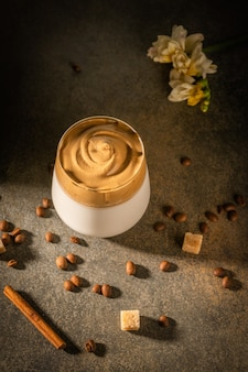Eigengemaakte dalgona-koffie op donkere achtergrond. naast koffiebonen, kaneel en rietsuiker.