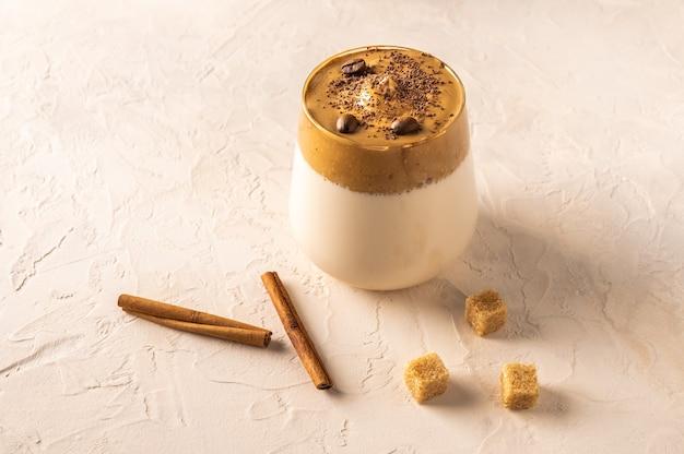 Eigengemaakte dalgona-koffie op lichte achtergrond. ernaast zijn kaneelstokjes en rietsuiker.
