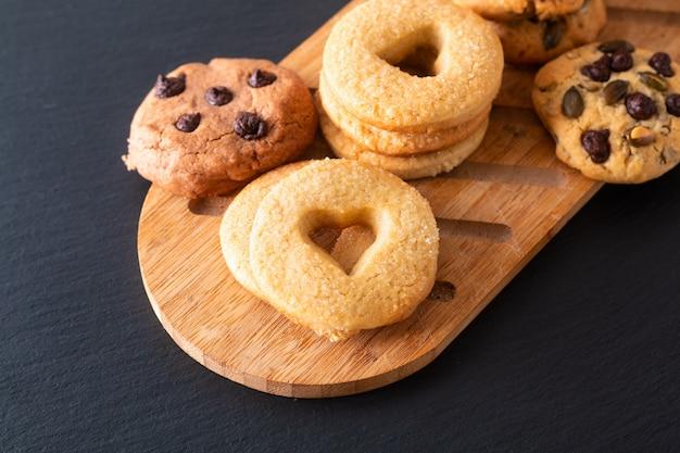 Eigengemaakte de suiker boterkoekjes van het voedselconcept op houten raad op de zwarte plaat van de leisteen met exemplaarruimte