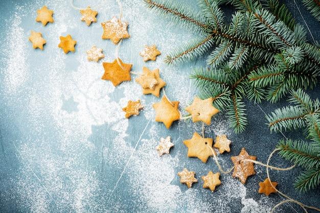 Eigengemaakte de vormsuiker van de zandkoekster met suikerpoeder en tak van pasvorm-boom op draad over blauwe textuuroppervlakte. kerstmis of nieuwjaar. bovenaanzicht met ruimte.