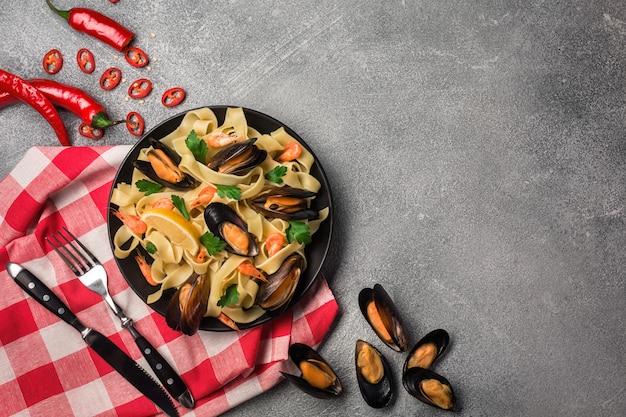 Eigengemaakte deegwarenspaghetti met mosselen, spaanse pepers en peterselie op steenachtergrond. zeevruchten maaltijd