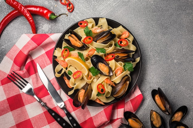 Eigengemaakte deegwarenspaghetti met mosselen, spaanse pepers en peterselie op steenachtergrond.