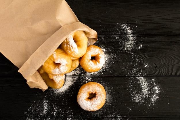 Eigengemaakte donuts met poedersuiker in het document pakket op de zwarte houten achtergrond. bovenaanzicht. kopieer ruimte.