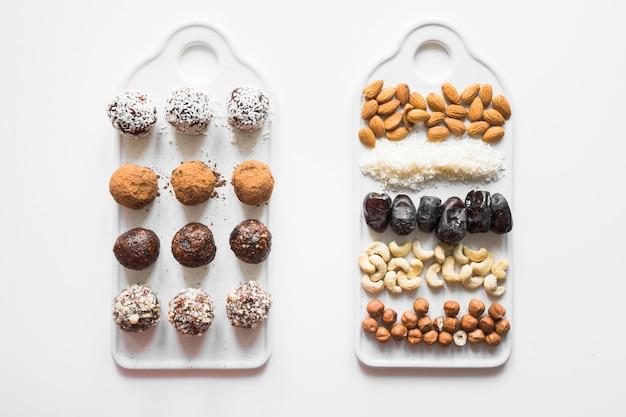 Eigengemaakte energieballen met cacao en noten op wit.