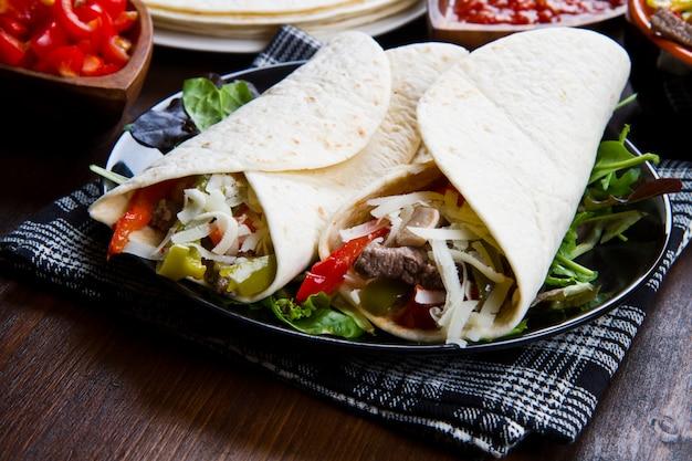 Eigengemaakte fajitas van de kip en van het rundvlees met groenten en tortilla's