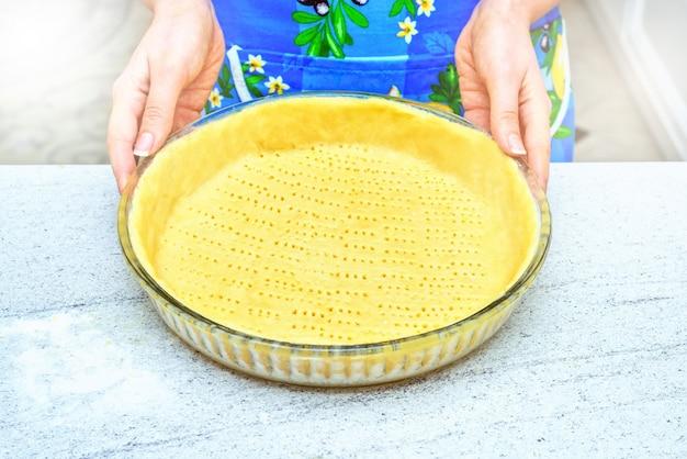 Eigengemaakte gebakjekorst. scherpe pastavoorbereiding, deeg op witte rustieke keukenlijst