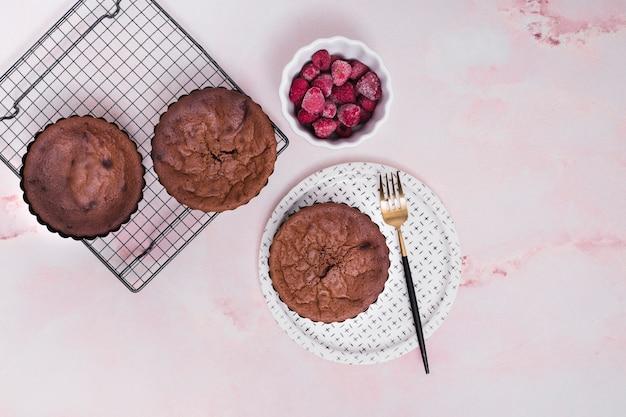 Eigengemaakte gebakken cakes op bakseldienblad en platen met bevroren frambozenkom tegen roze achtergrond