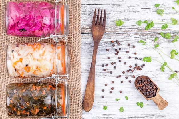 Eigengemaakte gemarineerde zuurkool zuur in glaskruiken op rustieke houten keukenlijst