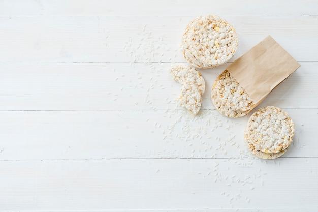 Eigengemaakte gepufte rijst met korrels op houten witte plank