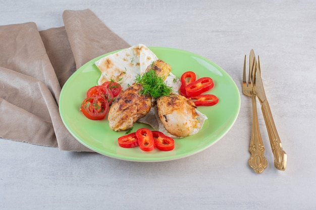 Eigengemaakte geroosterde kippenbenen met vlak brood op groene plaat.