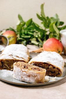 Eigengemaakte gesneden klassieke apfelstrudel met suikerglazuursuiker op ceramische plaat met verse hierboven appelen, groene bladeren en pijpjes kaneel. detailopname