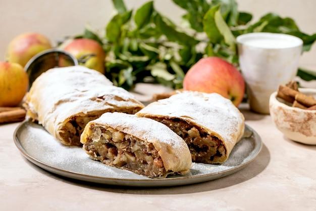 Eigengemaakte gesneden klassieke apfelstrudel met suikerglazuursuiker op ceramische plaat met verse hierboven appelen, groene bladeren en pijpjes kaneel.