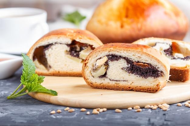 Eigengemaakte gistbroodjes met papaverzaden en honing op een houten zijaanzicht van de keukenraad.