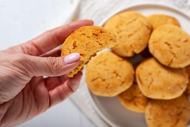 Eigengemaakte gouden bruine graankoekjes op een witte achtergrond met hand die één koekje, hoogste mening houdt