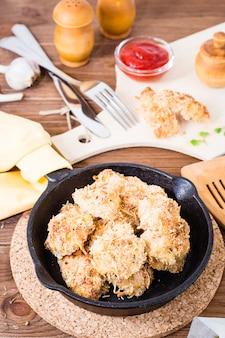 Eigengemaakte goudklompjes van kip in een ijzerpan