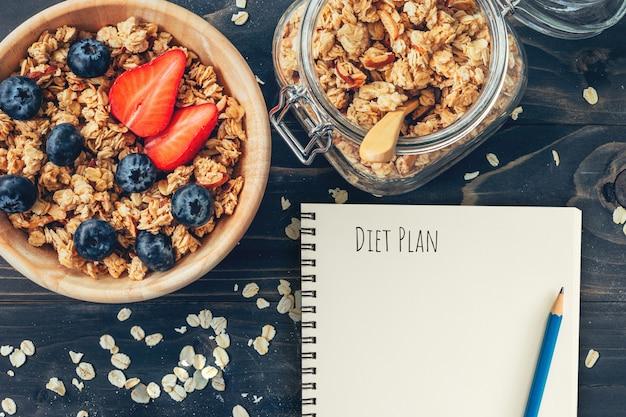 Eigengemaakte granola en verse bessen op houten lijst met van het notaboek en tekst het concept van het dieetplan, exemplaarruimte.