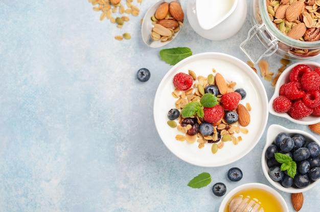 Eigengemaakte granola met yoghurt en verse bessen, gezond ontbijtconcept, hoogste mening, exemplaarruimte.