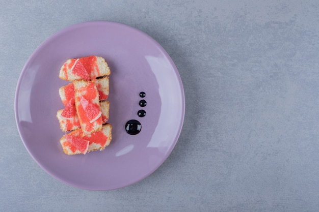 Eigengemaakte grapefruitcake op purpere plaat