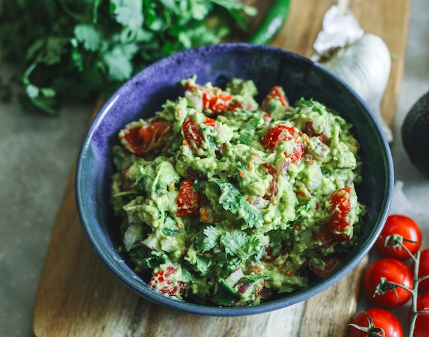 Eigengemaakte guacamole met het idee van het de fotografie recept van het kersentomatenvoedsel
