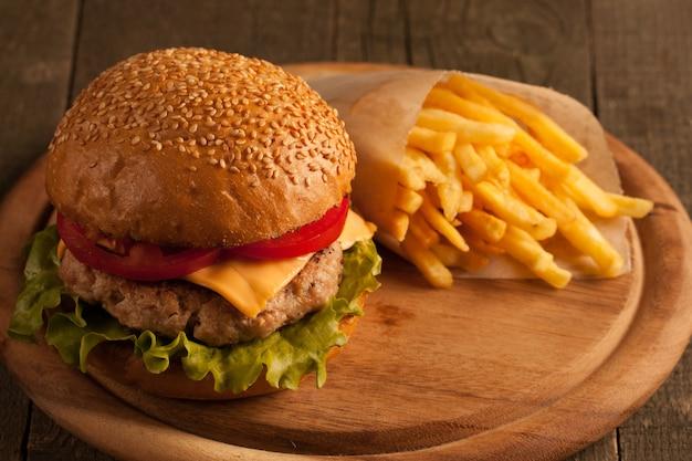 Eigengemaakte hamburger met rundvlees, ui, tomaat, sla en kaas. cheeseburger.