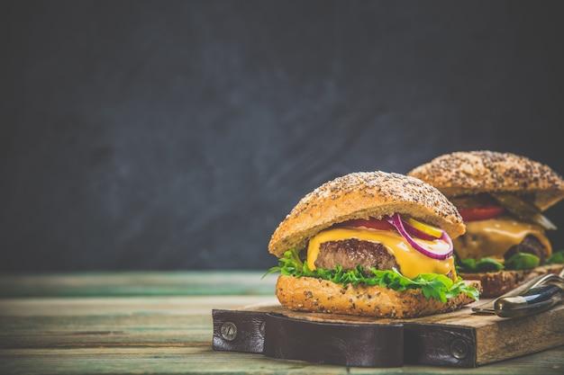 Eigengemaakte hamburgers op houten achtergrond, ruimte voor tekst