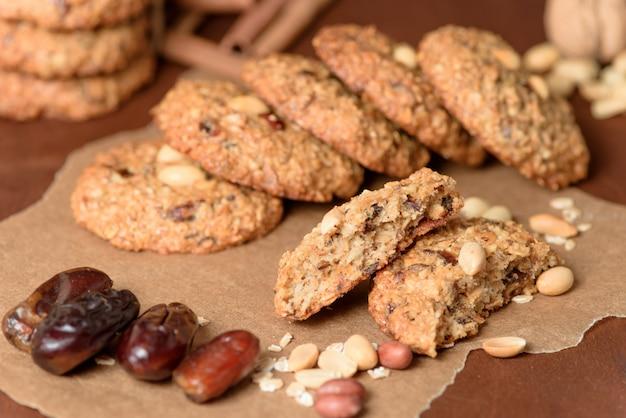 Eigengemaakte havermeelkoekjes met data, pinda's, kokosschaafsel op een houten achtergrond, macroclose-up. gebroken koekjes op de voorgrond