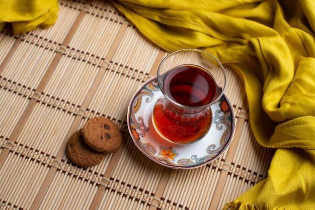 Eigengemaakte havermeelkoekjes met een kop thee met gele sjaal
