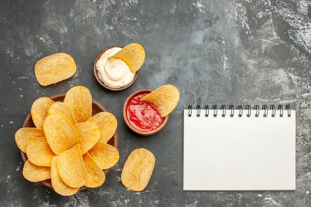 Eigengemaakte heerlijke chipsmayonaise met ketchup en notitieboekje op grijze lijst