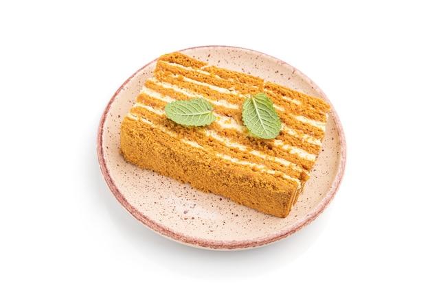 Eigengemaakte honingcake met melkroom en munt die op witte oppervlakte wordt geïsoleerd
