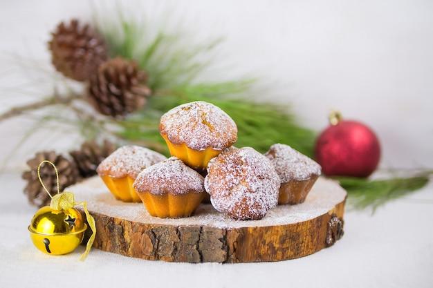 Eigengemaakte kerstmis cupcake, kerstmismuffins en nieuwe jaardecoratie en pijnboomtakken en kegels