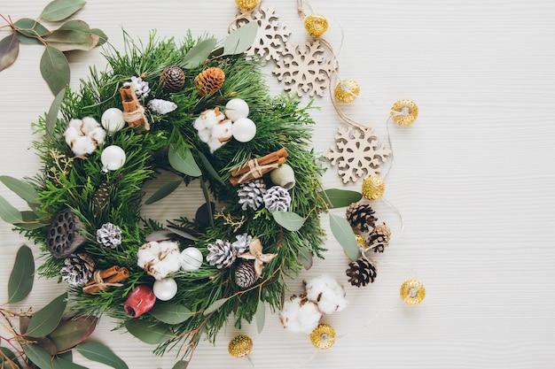 Eigengemaakte kerstmiskroon op witte houten lijst