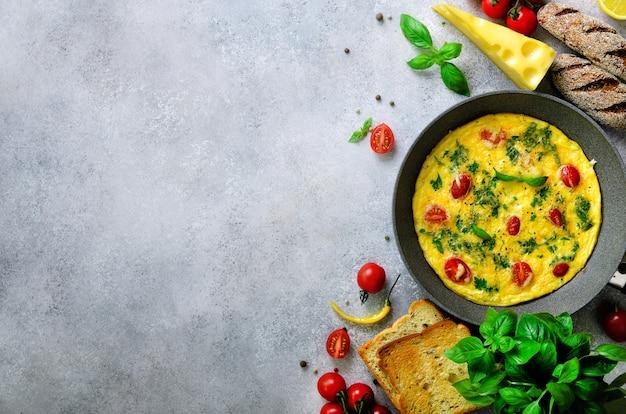 Eigengemaakte klassieke omelet met kersentomaten, kaas en kruiden op grijs beton. frittata in een koekenpan.