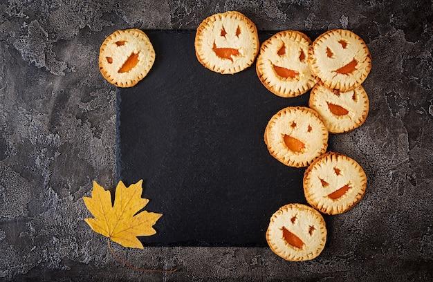 Eigengemaakte koekjes in de vorm als halloween-hefboom-o-lantaarn pompoenen op de donkere lijst.