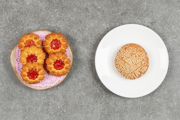 Eigengemaakte koekjes met gelei op houten stuk met sesamkoekje