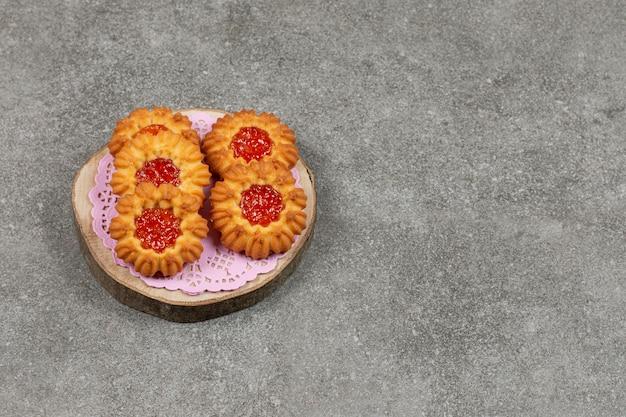Eigengemaakte koekjes met gelei op houten stuk