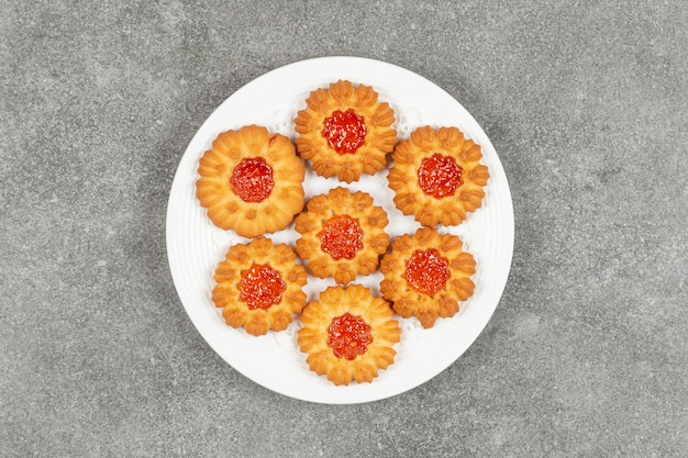 Eigengemaakte koekjes met gelei op witte plaat