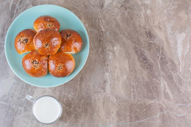 Eigengemaakte koekjes met melk op blauw bord over grijs.