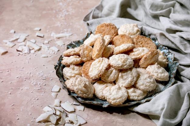 Eigengemaakte kokosnoot glutenvrije koekjes met kokosvlokken op ceramische plaat over roze textuuroppervlakte. kopieer ruimte