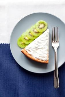Eigengemaakte kwark en griesmeelcake met kiwifruit en room op een plaat