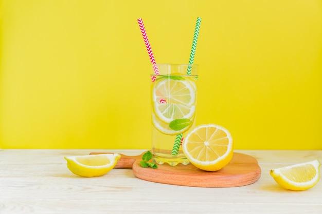 Eigengemaakte limonade met citroen en munt op gekleurde gele achtergrond. zomer koud drankje cocktail. copyspace
