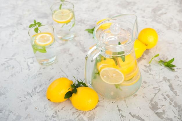 Eigengemaakte limonade op een licht concept als achtergrond. citroenen, glazen, mint, kruik en kopie ruimte. zomer verfrissend drankje limonade.