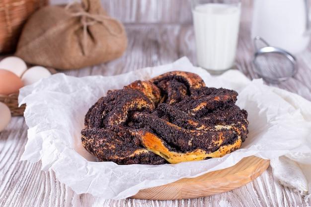 Eigengemaakte maanzaadtaart. gist ronde gesloten cake op een houten tafel met een linnen tafelkleed. kalach - rond brood.