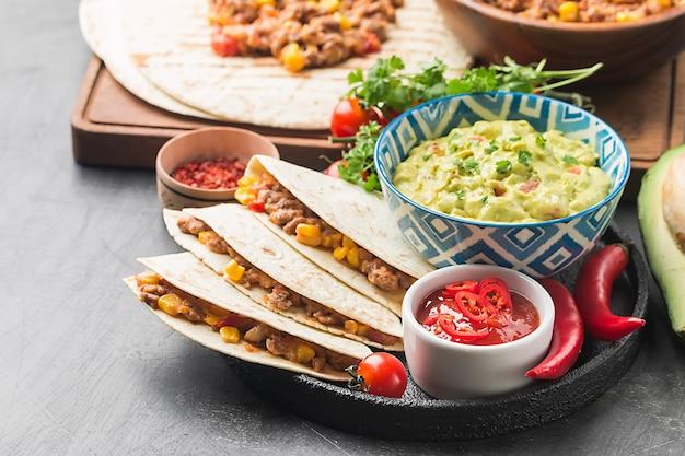 Eigengemaakte mexicaanse fajitas van rundvleesvlees met tortilla en guacamole en salsasauzen over zwarte oppervlakte