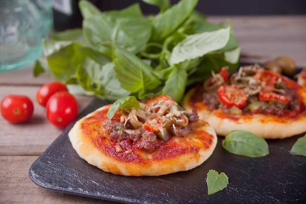 Eigengemaakte minipizza op de zwarte plaat.