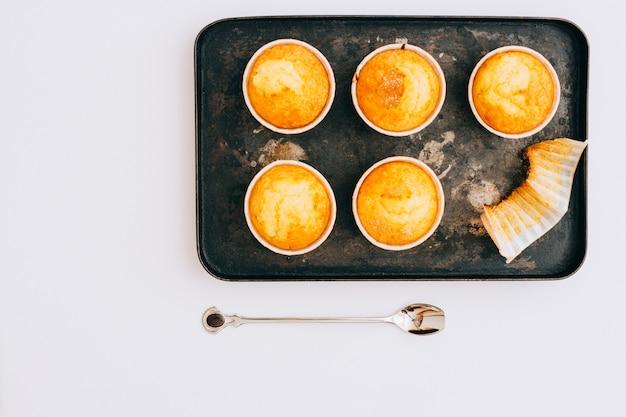 Eigengemaakte muffins in een zwart dienblad op een witte achtergrond