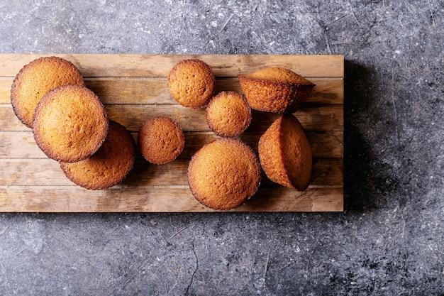 Eigengemaakte muffins op donkere textuurachtergrond. bovenaanzicht, plat gelegd. kopieer ruimte