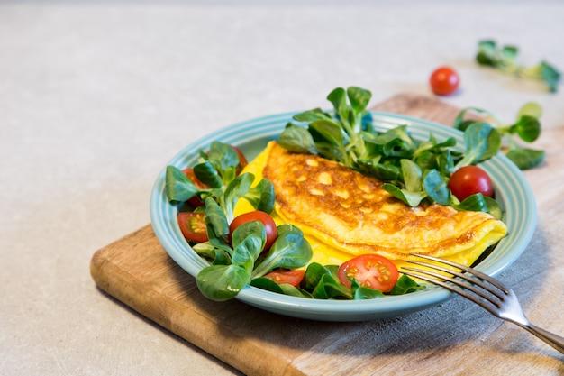 Eigengemaakte omelet met salade op plaat. gezond voedselconcept