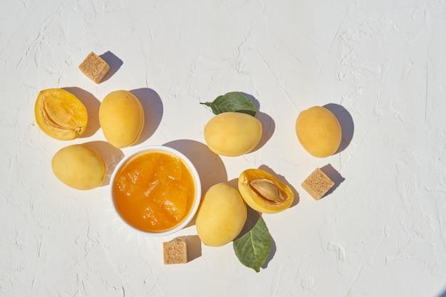Eigengemaakte organische abrikozenjam en rijpe abrikozen en bruine suiker op witte achtergrond.