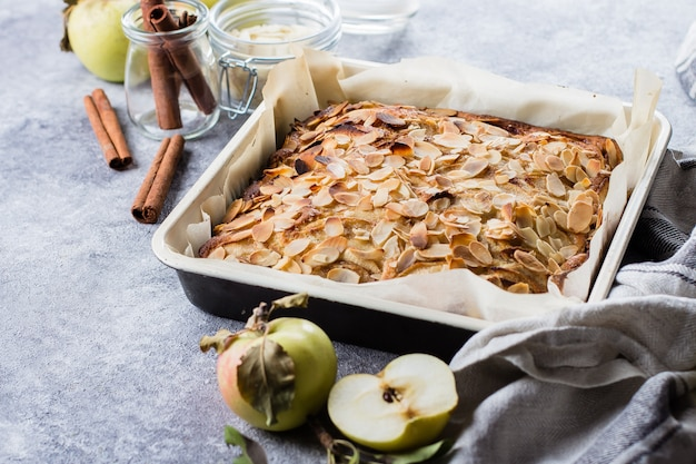 Eigengemaakte pastei met appelen en amandelvlokken op achtergrond van de steen de concrete lijst. scandinavië keuken