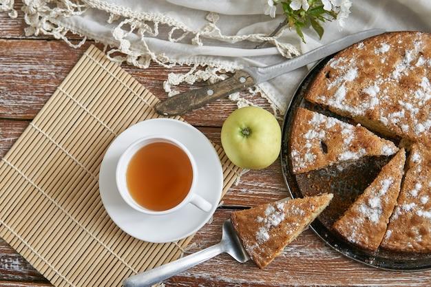 Eigengemaakte pastei met kersen en appelen witte kop thee op een donkere rustieke houten raadsachtergrond. eten in rustieke stijl